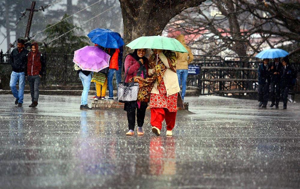 People walking with the umbrellas during heavy rain at Ridge in Shimla