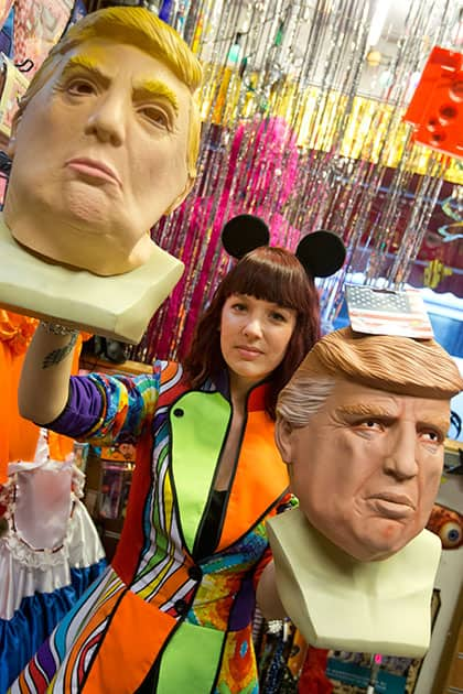 Chantal  poses with two masks of Donald Trump