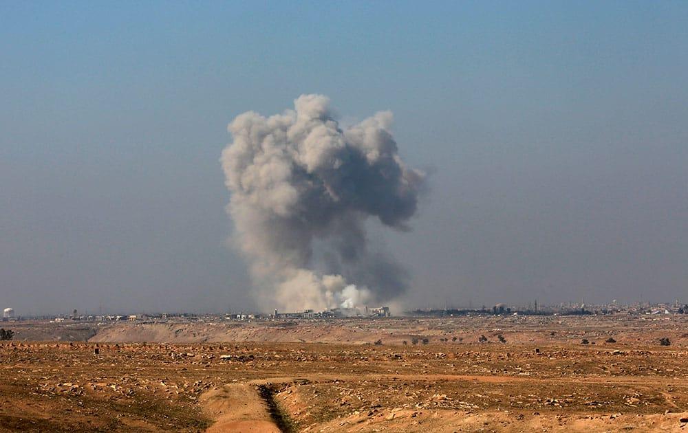 Smoke rises from the western side of Mosul following a U.S.-led coalition airstrike, in Abu Saif