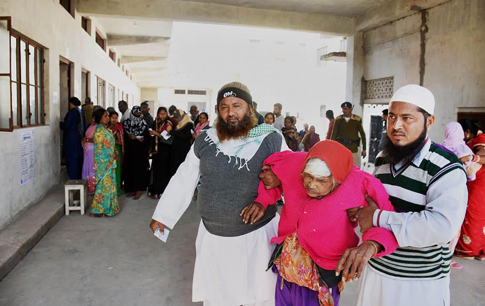 An elderly woman is helped by family members after she cast her vote for Assembly polls at a polling station in Ayodhya
