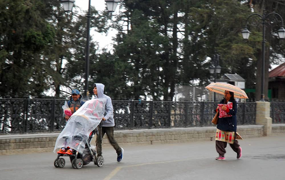 People walk on the Mall Road after it rained in Shimla