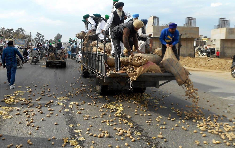 Farmers dump potatoes on a road