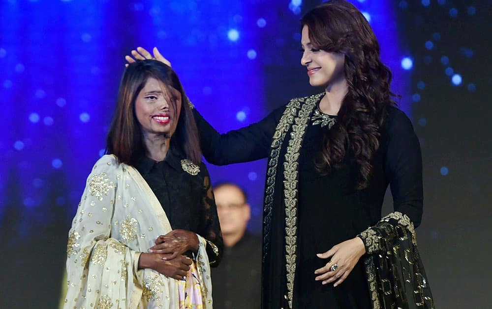 Juhi Chawla, walks on ramp with an acid attack victim