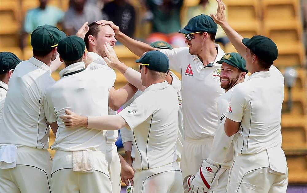 Josh Hazelwood with team mates celebrates the wicket of Virat Kohli