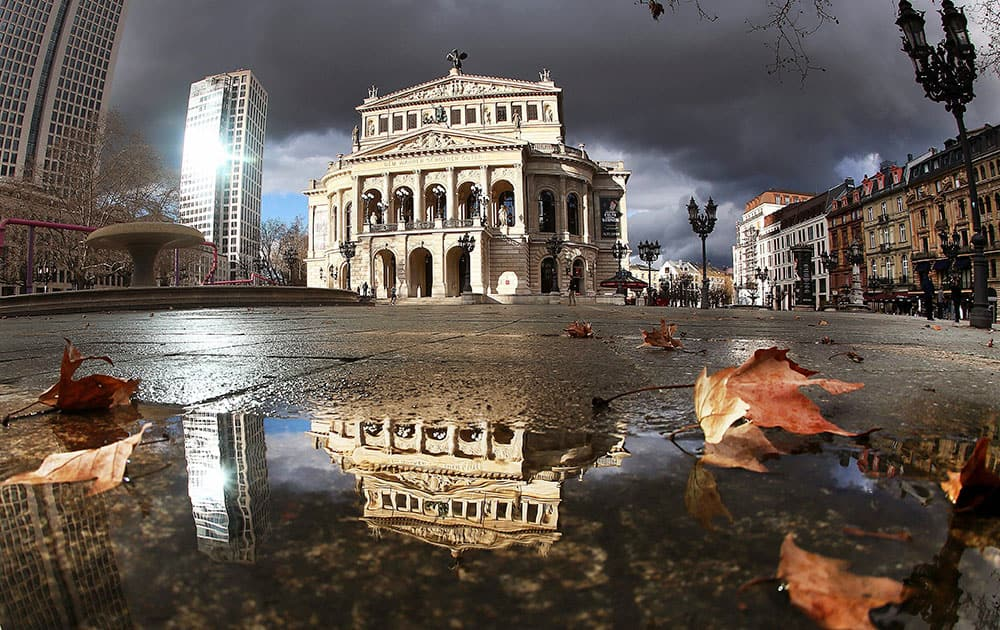 Dark clouds hang over the Old Opera which is spotlighted by the sun