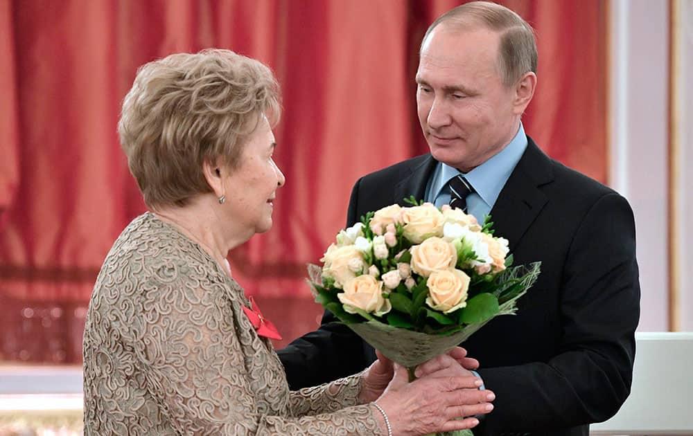 Vladimir Putin gives flowers to Naina Yeltsin at a reception marking her 85th birthday