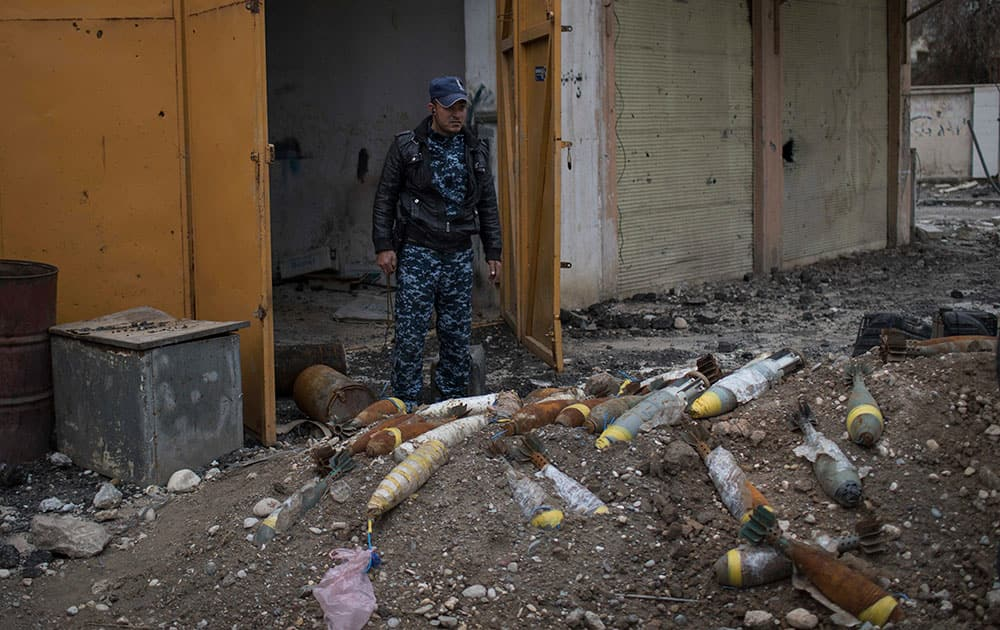 A Federal Police stands next to unexploded bombs left by Islamic State militants