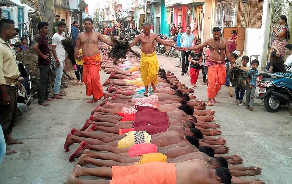 A priest walks over devotees during Danda yatra