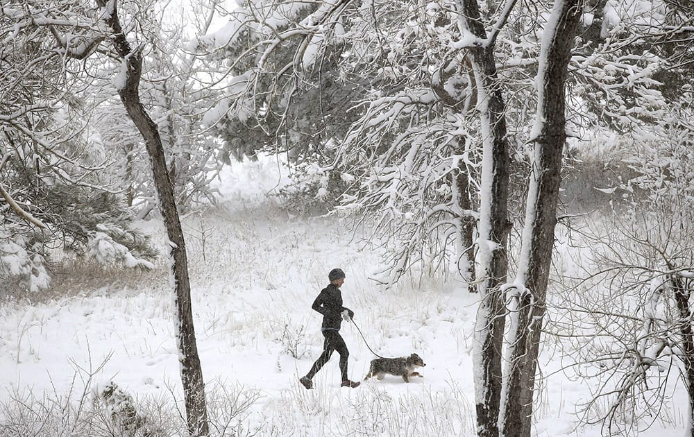 A woman and her dog run in snow following an overnight storm in Boulder