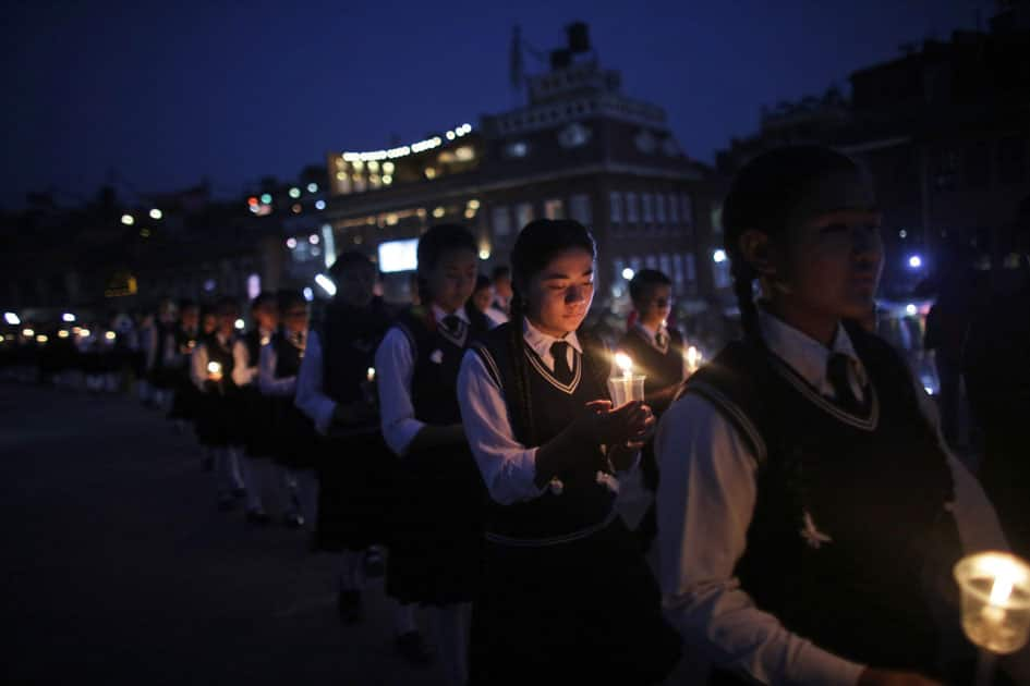 Nepalese students hold lighted candles