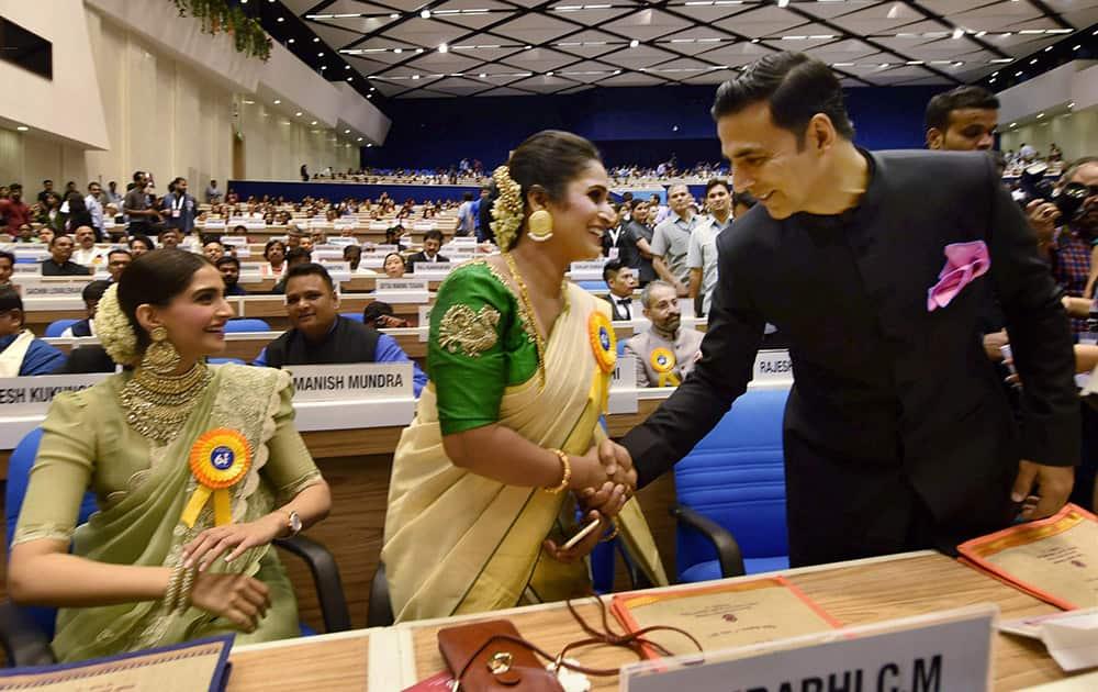 Best Actor award winner Akshay Kumar shakes hands with Best actress award winner Surabhi Jyoti at the 64th National Film Awards function