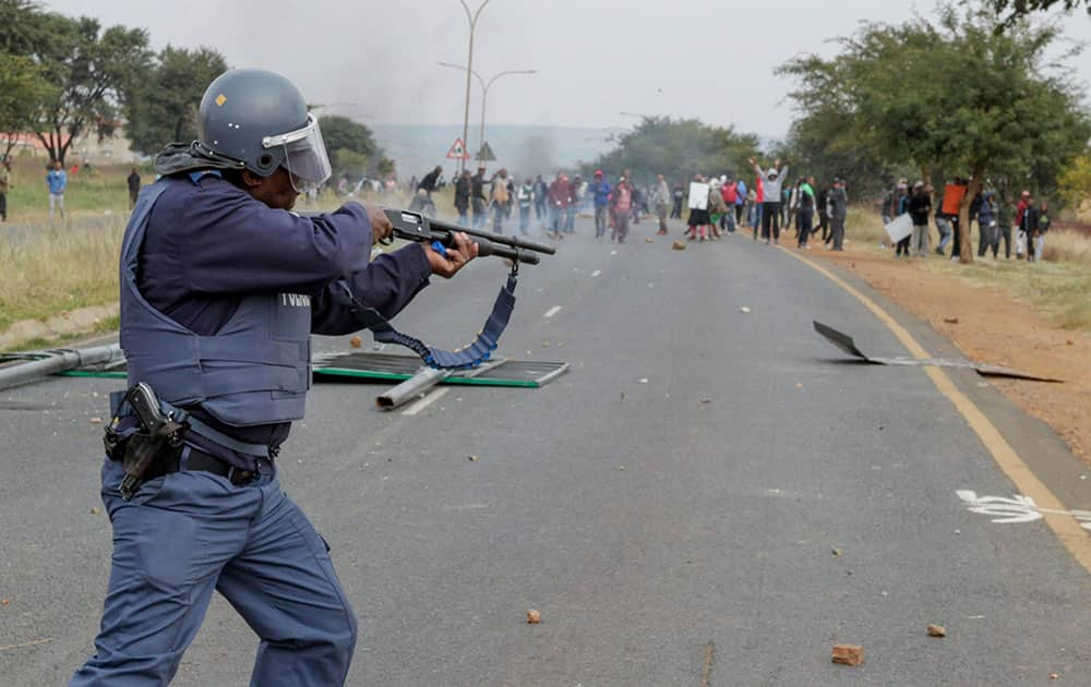 A policeman fires rubber bullets at protesters in Johannesburg