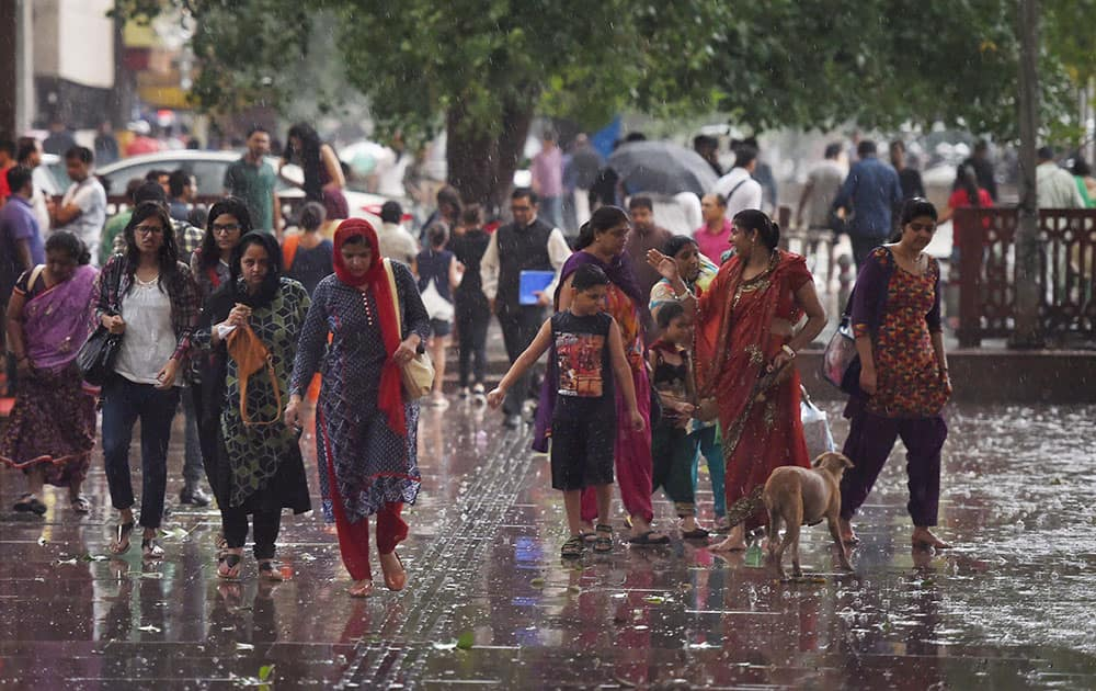 People walk at Connaught Place area during rains