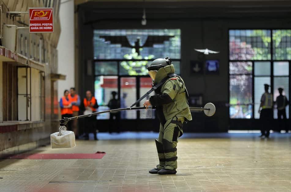 A Romanian explosives specialist handles a suspicious package