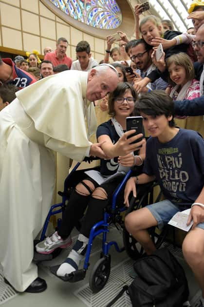 Pope Francis poses for a picture with youths