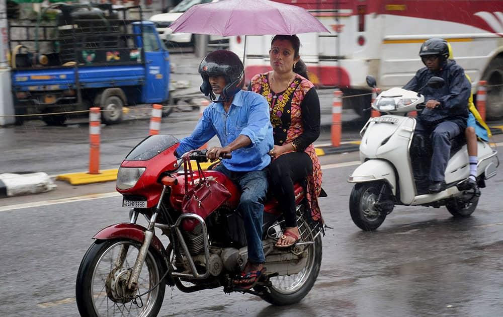 Bikers wade through as it rains in Guwahati