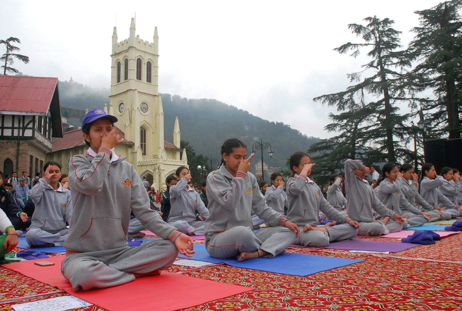 Yoga practitioners participate in a mass yoga session