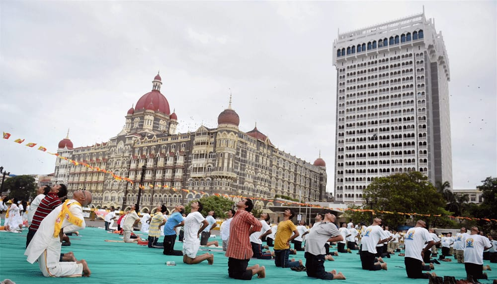 People perform yoga during a mass yoga event