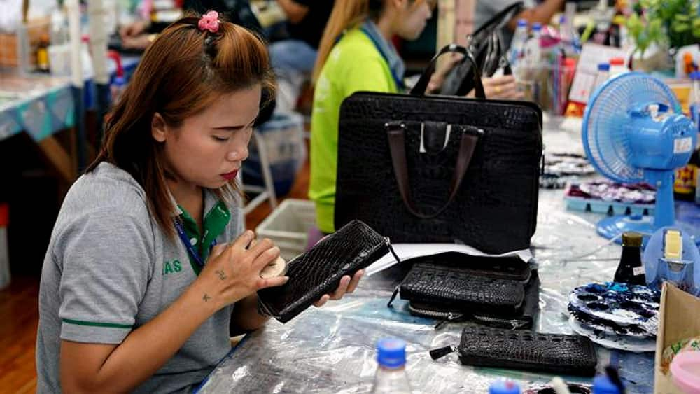 A worker polishes a wallet made from crocodile skin
