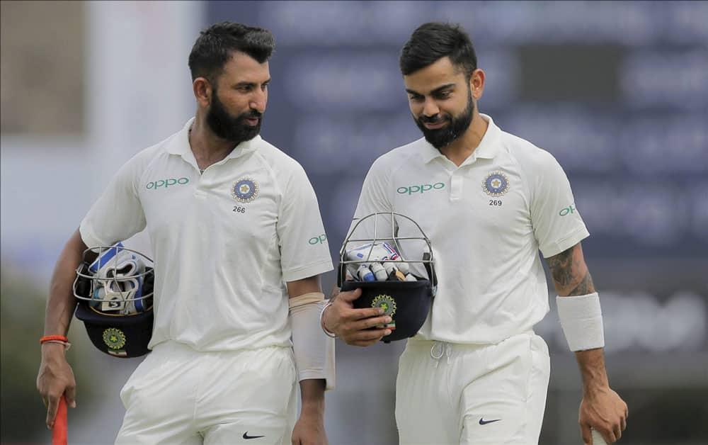 captain Virat Kohli and Cheteshwar Pujara walk off
