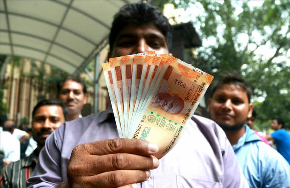 A man shows the new Rs 200 currency note