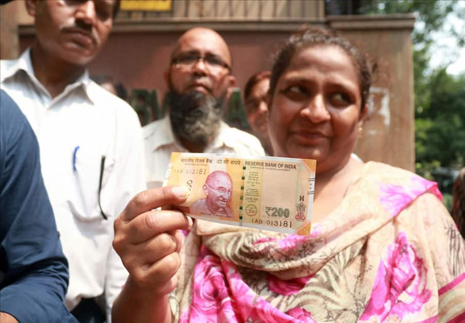 A woman shows the new Rs 200 currency note