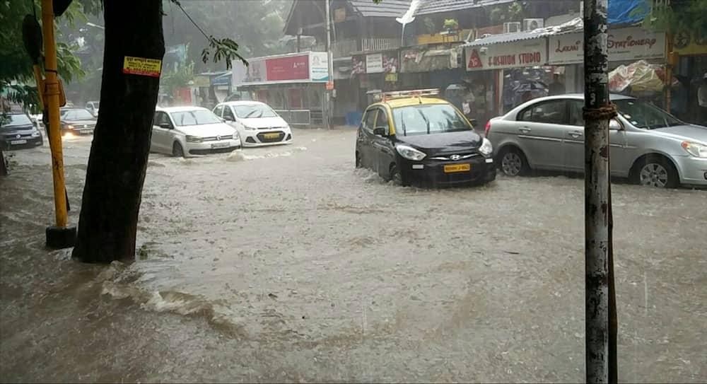 Vehicles struggle through a water-logged street