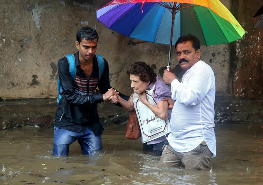 A woman is helped to move through a water-logged road