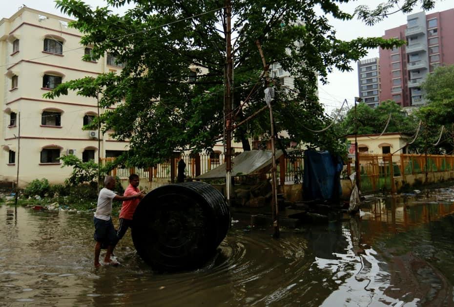 Men push a water tank through partially flooded street
