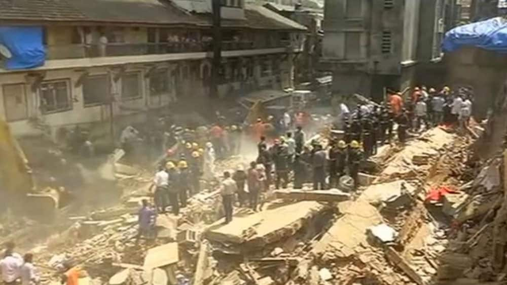 People and rescue personnel are seen after a building collapsed