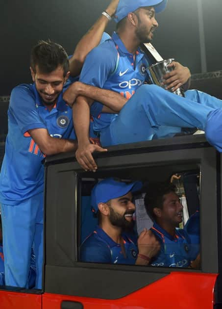 India's captain Virat Kohli, takes a ride in a vehicle with fellow team members
