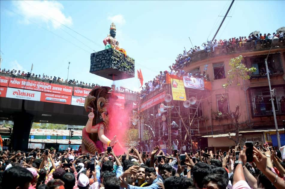 Devotees gather as a Ganesh idol is being taken for immersion