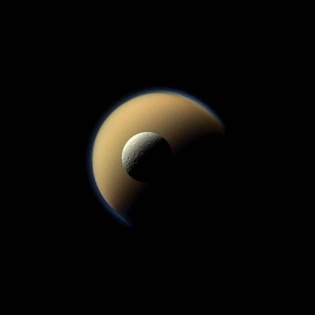 Saturn's largest and second largest moons, Titan and Rhea, appear to be stacked on top of each other in this true-color scene from NASA's Cassini spacecraft