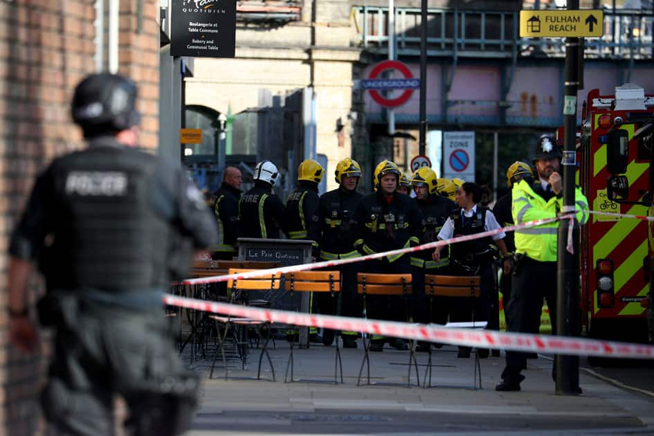 Members of the London Fire Brigade stand by cordon near Parsons Green tube station in London