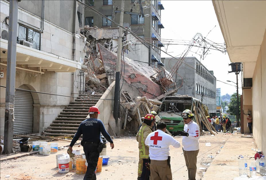 Rescuers work at a collapsed building after an earthquake in Cuernavaca City, Morelos State, Mexico