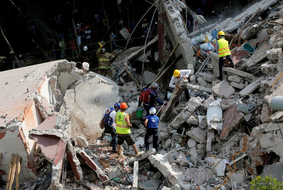 Rescue personnel remove rubble at a collapsed building while searching for people after an earthquake hit Mexico City, Mexico