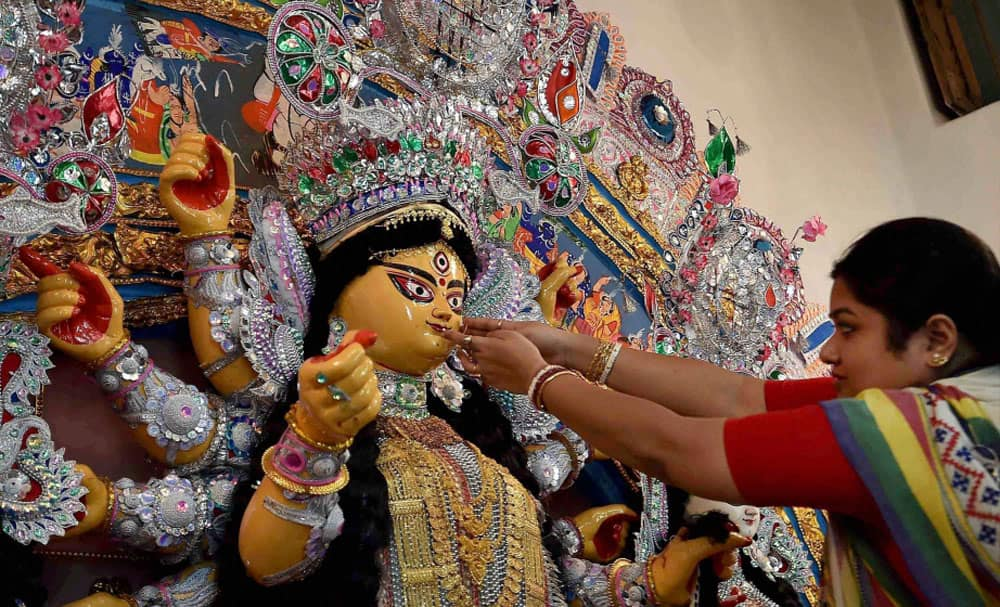 An idol of Goddess Durga being being decorated with gold ornaments during Durga Puja festival in Kolkata.