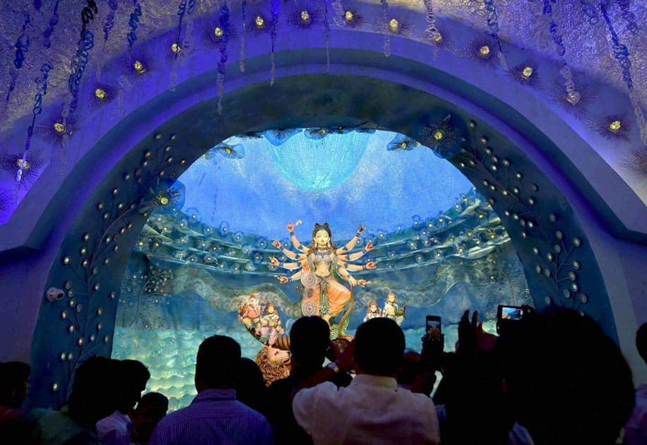 Visitors taking pictures of the Devi Durga idol installed at a community puja pandal in Kolkata.