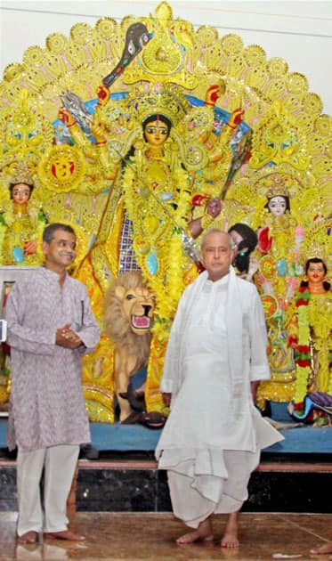 Former President of India Pranab Mukherjee with his son and MP Abhijit Mukherjee standing in front of idol of Goddess Durga at his ancestral home in Mirati village in Birbhum district of West Bengal.