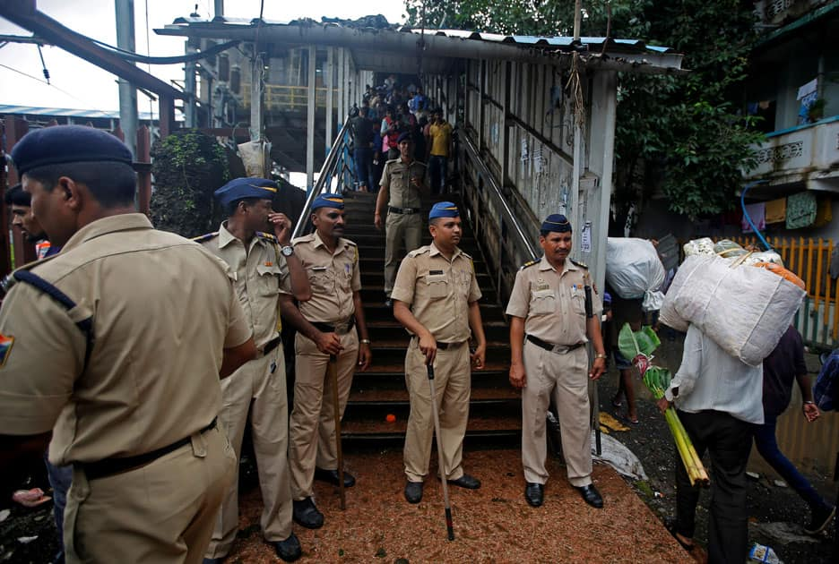 Policemen inspect the site of a stampede at a railway station's pedestrian overbridge in Mumbai.