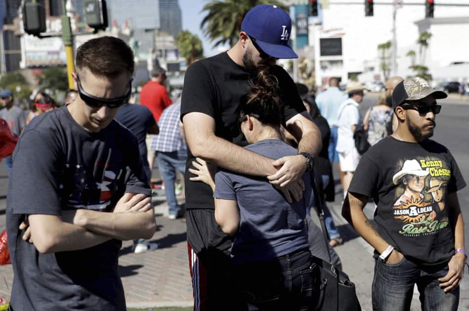Reed Broschart, center, hug his girlfriend Aria James on the Las Vegas Strip in the aftermath of a mass shooting at a concert in Las Vegas.
