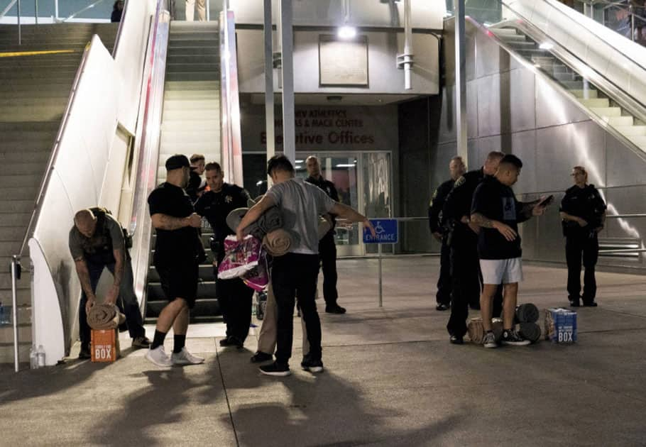 Metro Police conduct a search on people bringing supplies to the people taking refuge inside the Thomas & Mack following a mass shooting at the Route 91 music festival in Las Vegas.