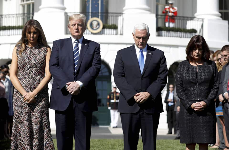 President Donald Trump and first lady Melania Trump stand with vice president Mike Pence and his wife Karen during a moment of silence to remember the victims of the mass shooting in Las Vegas.