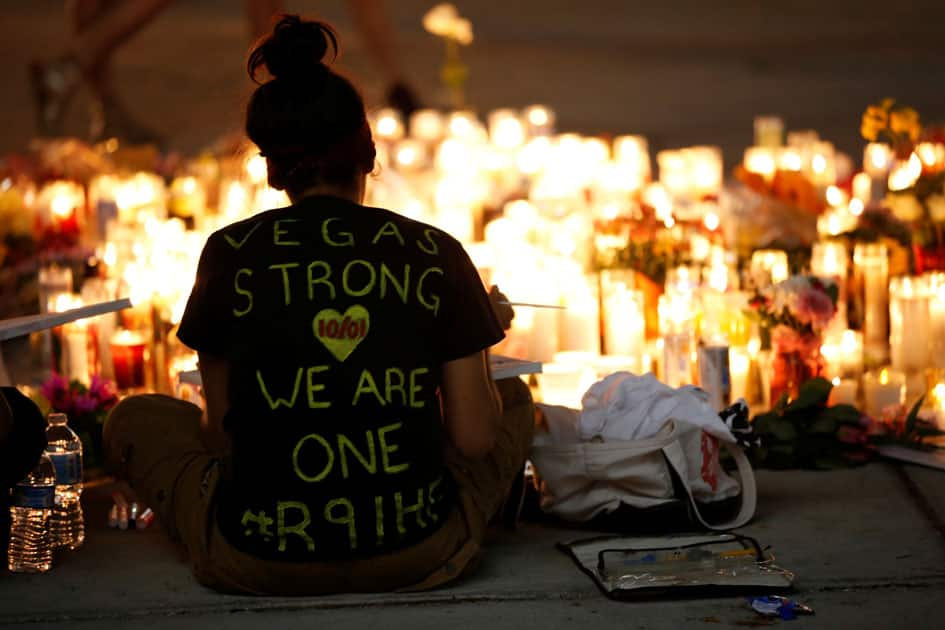 A woman makes a sign at a vigil on the Las Vegas strip following a mass shooting at the Route 91 Harvest Country Music Festival in Las Vegas.