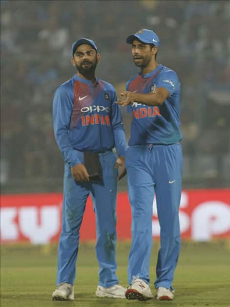 Indian skipper Virat Kohli interacts with Ashish Nehra during the first T20 match between India and New Zealand at Feroz Shah Kotla stadium in New Delhi.