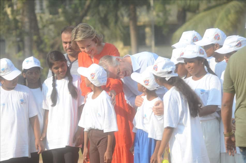 Belgium's King Philippe and Queen Mathilde and former Indian cricketer Virender Sehwag play cricket with under privileged children during an event hosted by UNICEF in Mumbai.