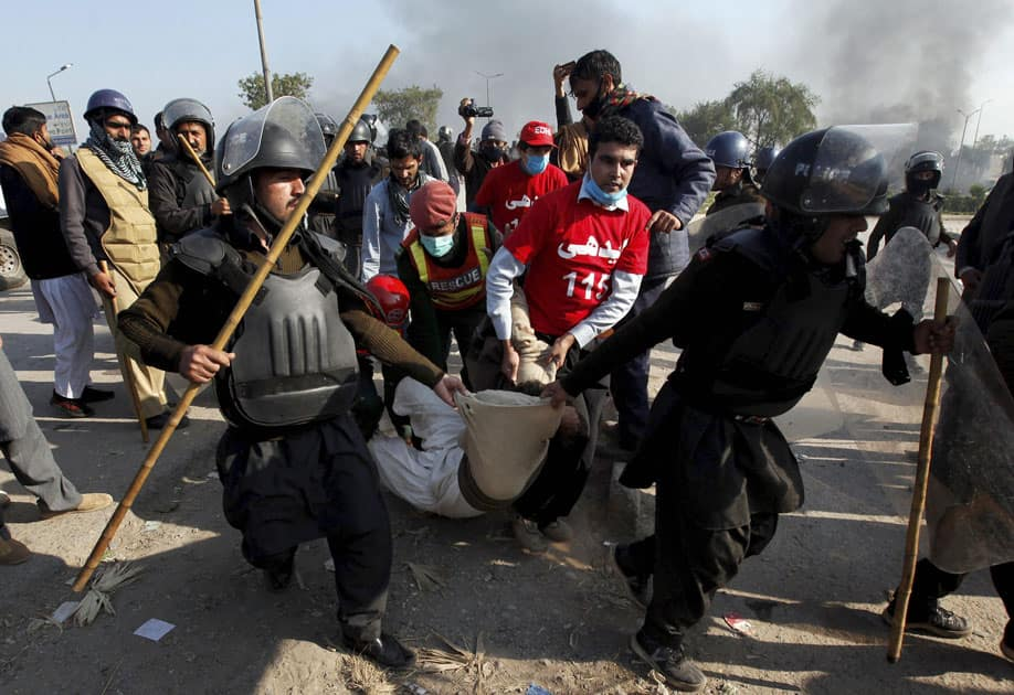 Pakistani police officers carry an injured protester during a clash in Islamabad, Pakistan.