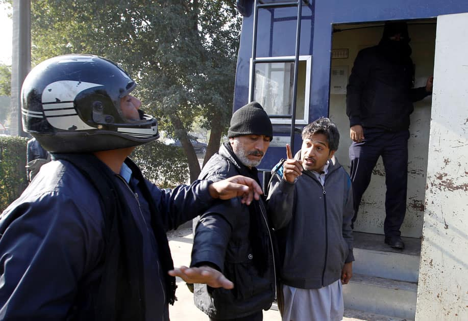 A demostrator detained by police gestures after being hit by a policeman as he is led to a police van near the Faizabad junction in Islamabad.