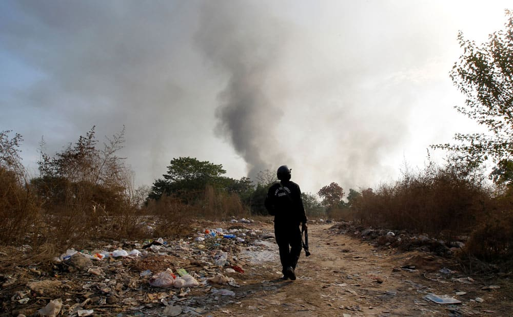 A policeman walks towards clashes with demonstrators near the Faizabad junction in Islamabad.