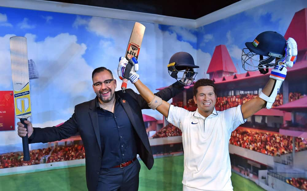 Merlin Entertainments' director of new openings in emerging markets, poses with the wax figure of Sachin Tendulkar which was displayed at Madame Tussauds Wax Museum, during a press preview in New Delhi.